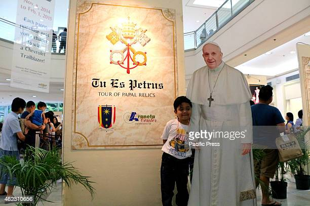 A young child poses for a picture beside the standee of Pope Francis in a 'Tour of Papal Relics' exhibit inside the Gateway Mall Cubao Quezon City...
