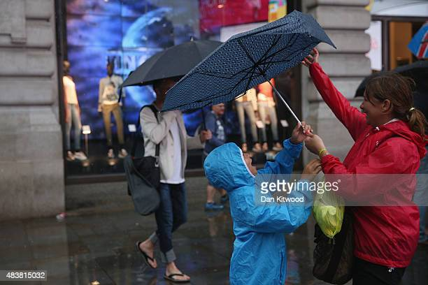 A young child reaches for an umbrella in heavy rain on August 13 2015 in London England The Met Office has issued an amber warning for heavy rain in...