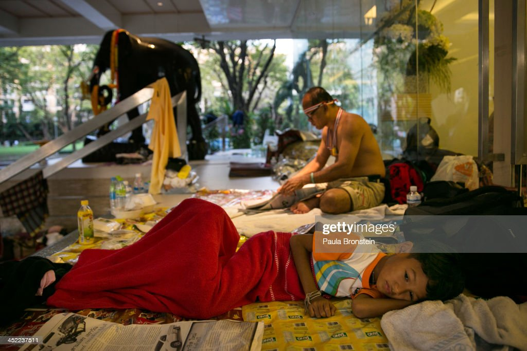 A young child rests next to her family as anti-government protesters occupy the Finance ministry for a third day in a bid to oust the current government of Yingluck Shinawatra on November 27, 2013 in Bangkok, Thailand. Protests have been building for weeks and continue to remain peaceful as protesters attempt to occupy more government buildings. However, the Prime Minister of Thailand, Yingluck Shinawatra, has announced the use of a special security law to counter demonstrators who stormed into government departments today.