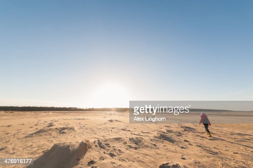 Young child running on a wild deserted beach