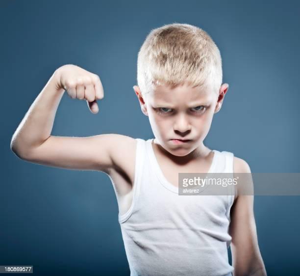 Junge Kind zeigt seine Muskeln