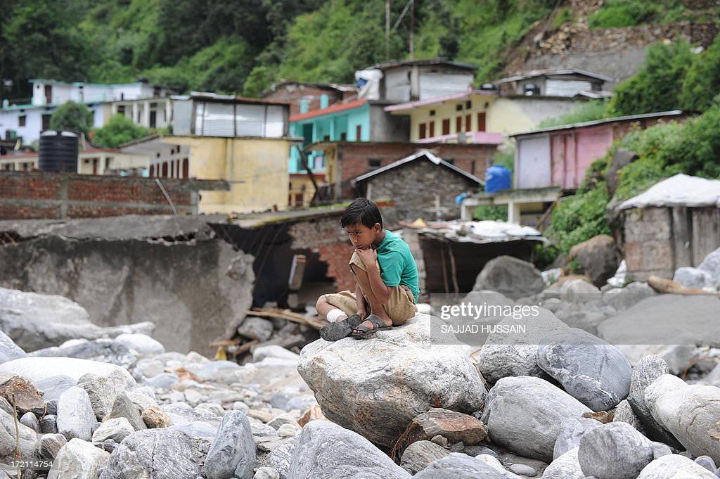 A young child sits on boulders in Sonprayag on July 2, 2013, in a flood affected area of the northern Indian state of Uttrakhand. Construction along river banks will be banned in a devastated north Indian state amid concerns unchecked development fuelled last month's flash floods and landslides that killed thousands, the state's top official said. The Chief Minister of Uttarakhand, Vijay Bahuguna, also announced that a regulatory body would be set up to scrutinise future construction as the Himalayan state begins the herculean task of rebuilding following the June 15 floods.