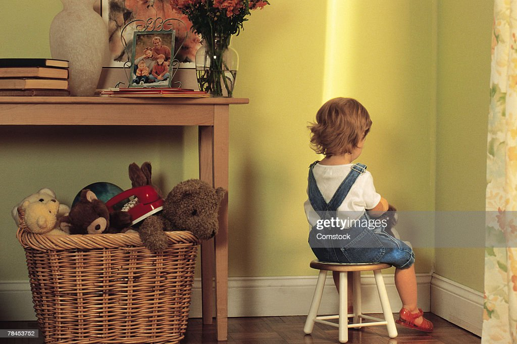 Young child sitting in corner as punishment : Stock Photo