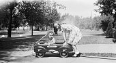 Young child sitting inside toy Playboy Wagon while young girl in summer dress prepares to push the vehicle along In the background is a hose watering...