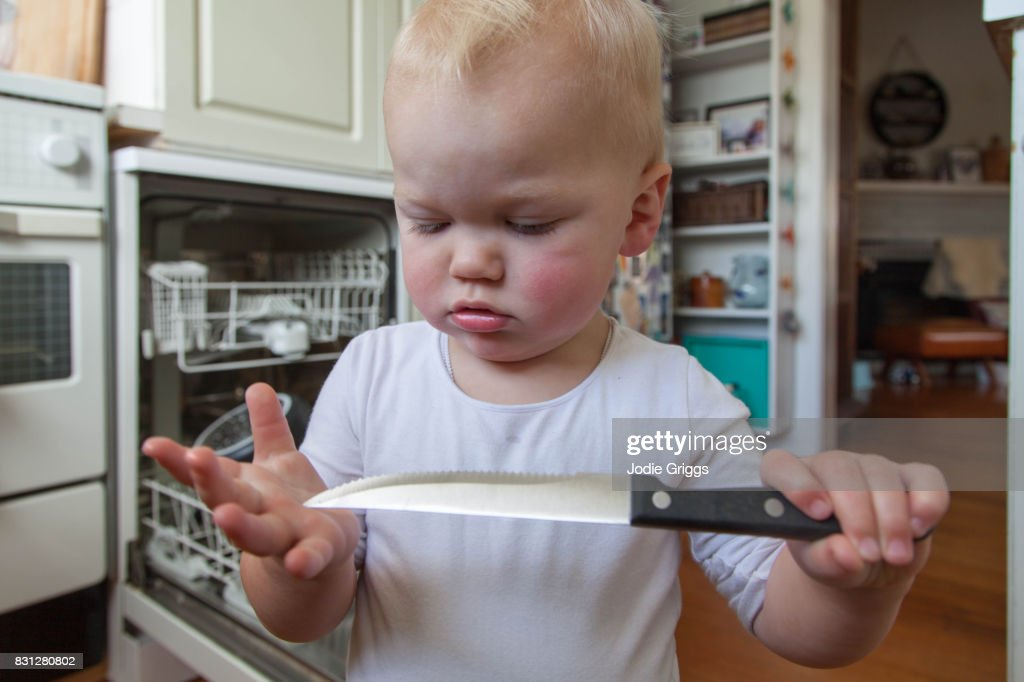 Young Child Standing In The Kitchen Playing With A Sharp Knife ...