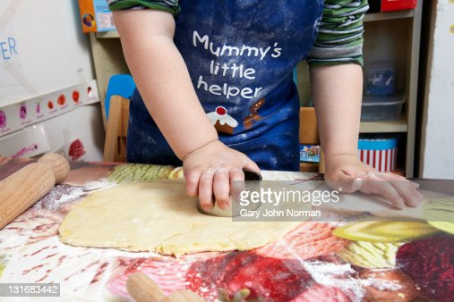 Young child using cookie cutter. : Stock Photo