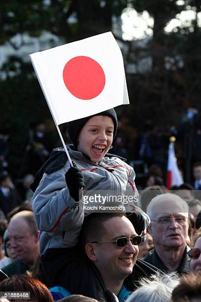 A young child waves a Japanese flag and he and others cheer during a ceremony to celebrate Emperor Akihito's 71st birthday at the Imperial Palace...