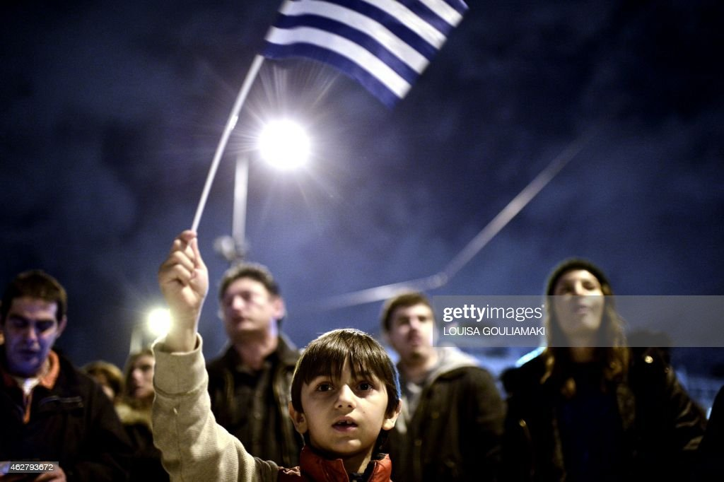 A young child waves the national flag as crowds gather in front of the Greek parliament in Athens on February 5 2015 in support of the new...