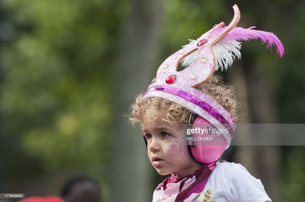 A young child wearing a feathered head-dress watches the first day of the Notting Hill Carnival in west London on August 25, 2013. Running over two days, the Caribbean carnival puts on a Kid's day on the Sunday when costume prizes are awarded and a 'main parade' day on the Monday.