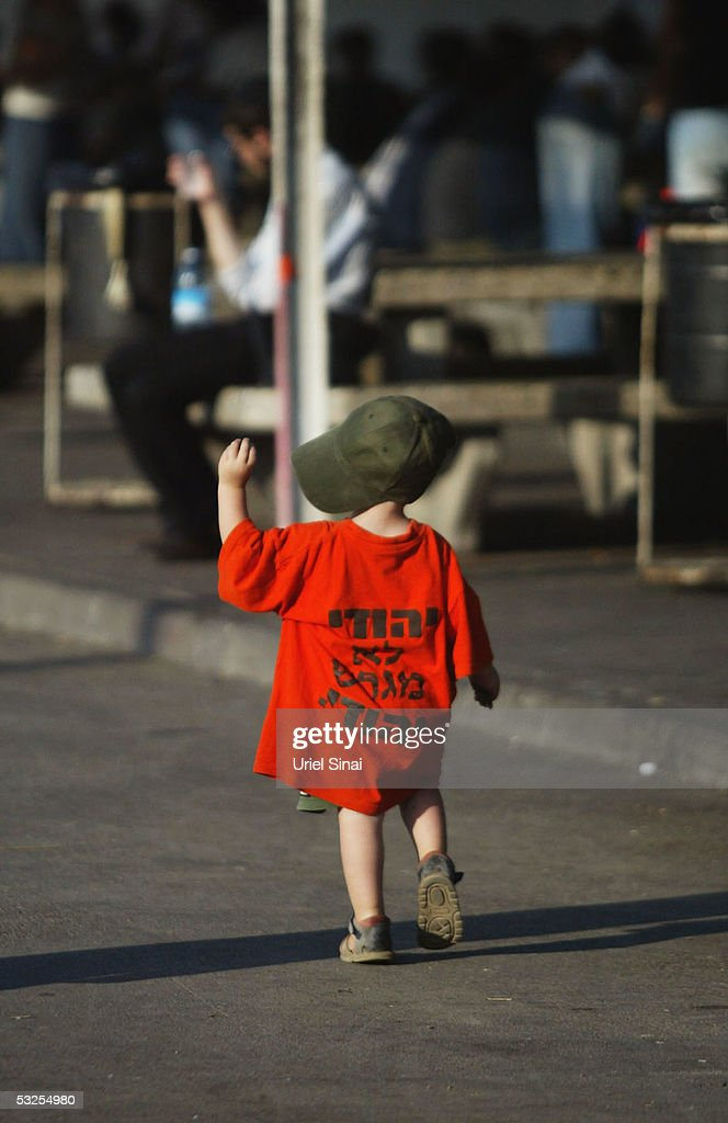 A young child wearing the orange colours of the opponents to Israeli Prime Minister Ariel Sharon's disengagement plan walks down the street amid the...