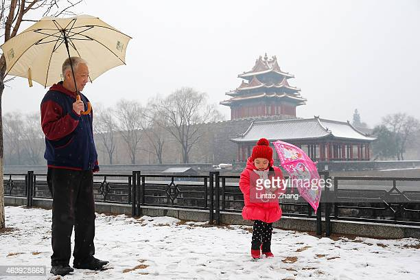 A young child with her grandfather plays in the snow outside the Forbidden City falls on February 20 2015 in Beijing China China celebrated its new...
