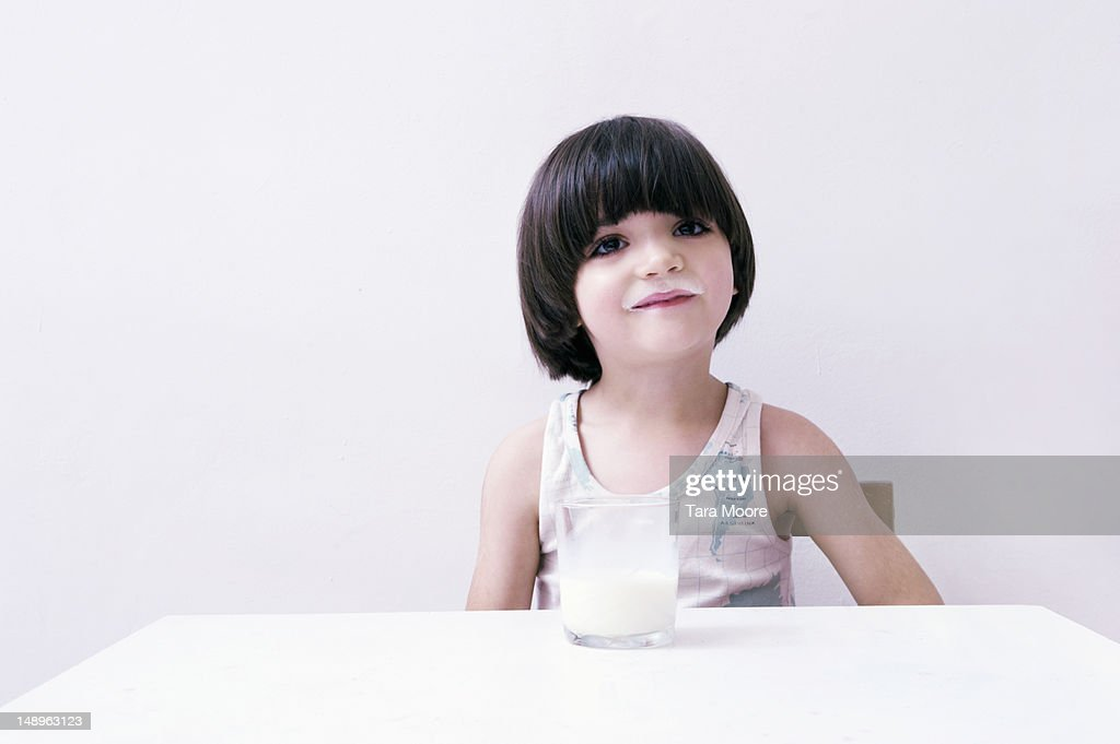 young child with milk moustache and glass