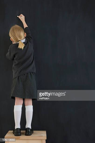 Young child writing on a chalkboard