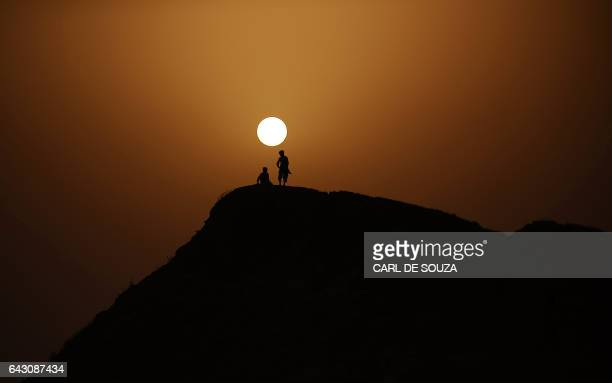 Young children are silhouetted as the sun sets outside a Pakistani army run relief camp in Sehwan on September 16 2010 Antonio Guterres of the UN...