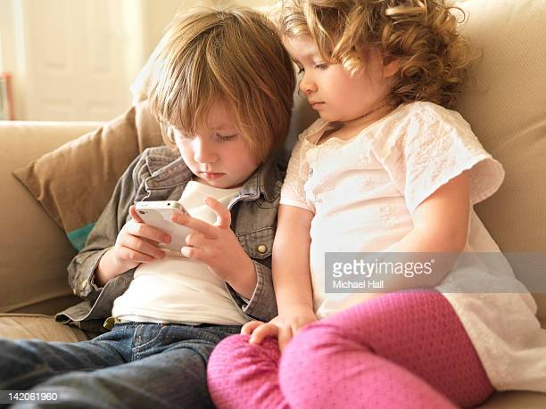 Young children at home viewing tablet