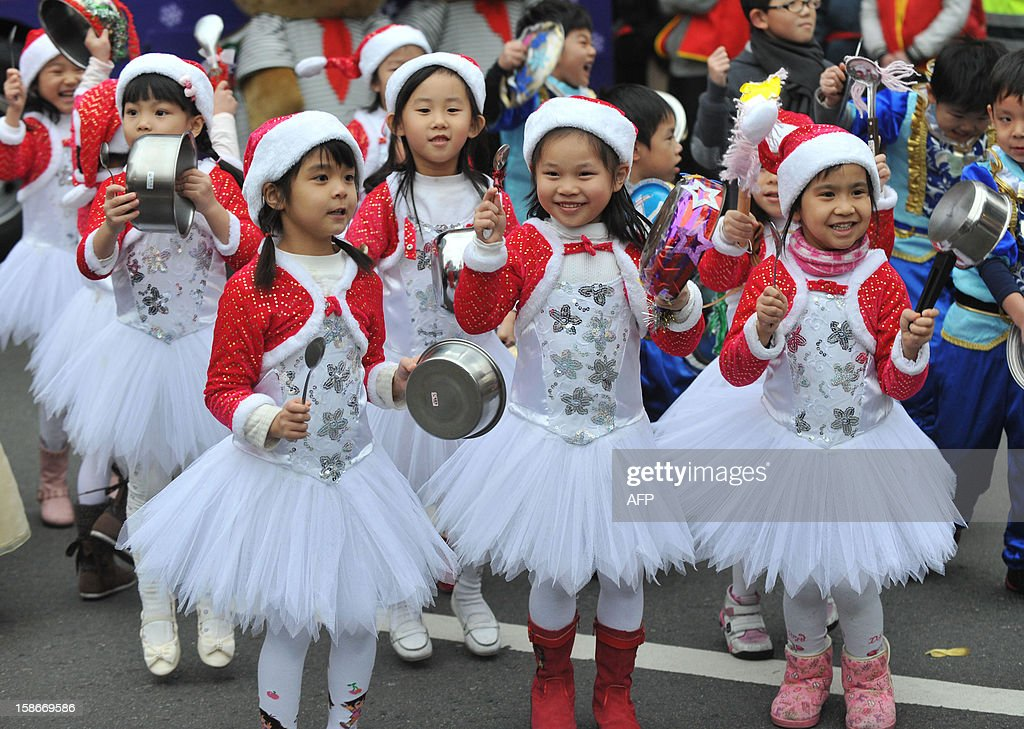 Young children dressed up in Christmas outfits bang pans to make noise during a parade in Taipei on December 23, 2012. A total of 34 teams took part in the Christmas parade procession to celebrate the upcoming Christmas. AFP PHOTO / Mandy CHENG