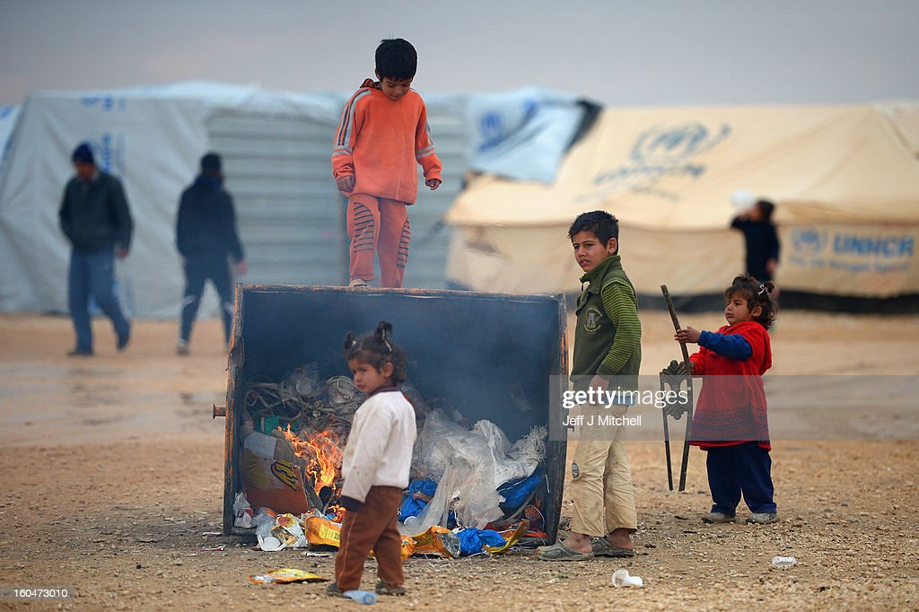 ZA'ATARI, JORDAN - FEBRUARY 01: Young children get a heat from a burning rubbish bin as Syrian refugees go about their daily business in the Za'atari refugee camp on February 1, 2013 in Za'atari, Jordan. Record numbers of refugees are fleeing the violence and bombings in Syria to cross the borders to safety in northern Jordan and overwhelming the Za'atari camp. The Jordanian government are appealing for help with the influx of refugees as they struggle to cope with the sheer numbers arriving in the country.
