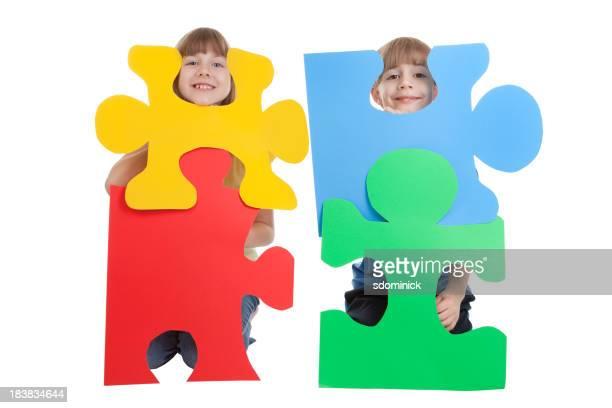 Junge Kinder halten bunte Puzzle-Stücke