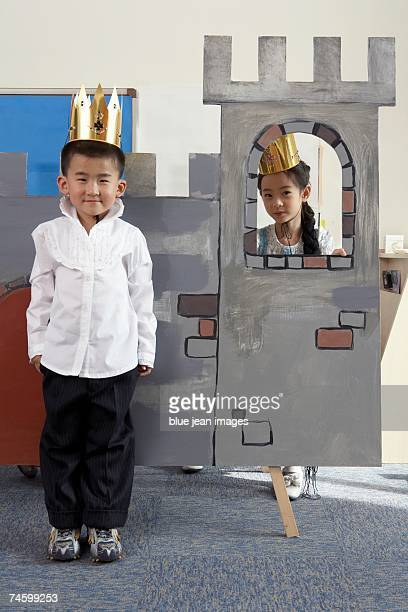 Young children in a play pose on their set.