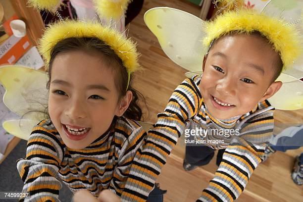 Young children in costumes reach for the camera.