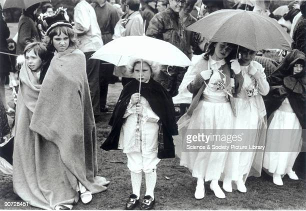 Young children in fancy dress holding up umbrellas at the Chatham May Queen Festival Kent Photograph by Tony RayJones who created most of his images...