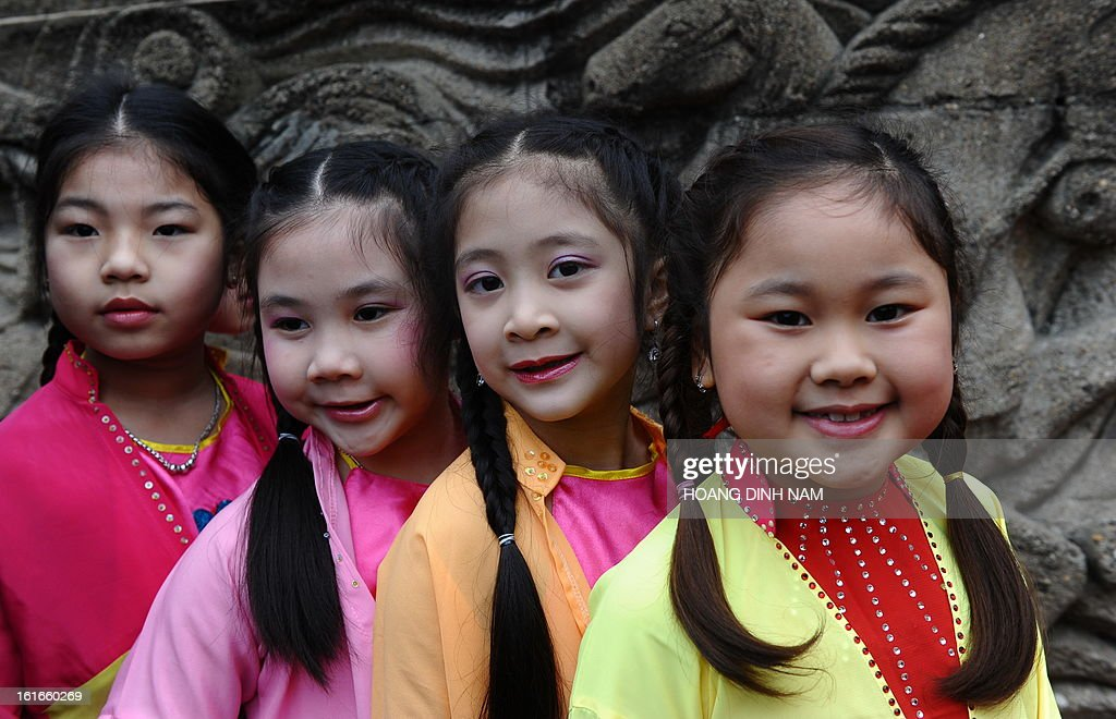 Young children in festive dress wait to perform during a ceremony to mark the 224th anniversary of Vietnam's Dong Da victory over Chinese invading troops in the spring of 1789 at the site of the historical battlefield in Hanoi on February 14, 2013. AFP PHOTO/HOANG DINH Nam