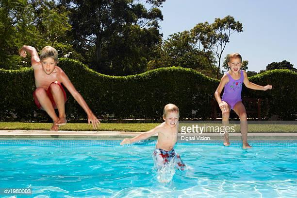 Young Children Jumping into a Swimming Pool