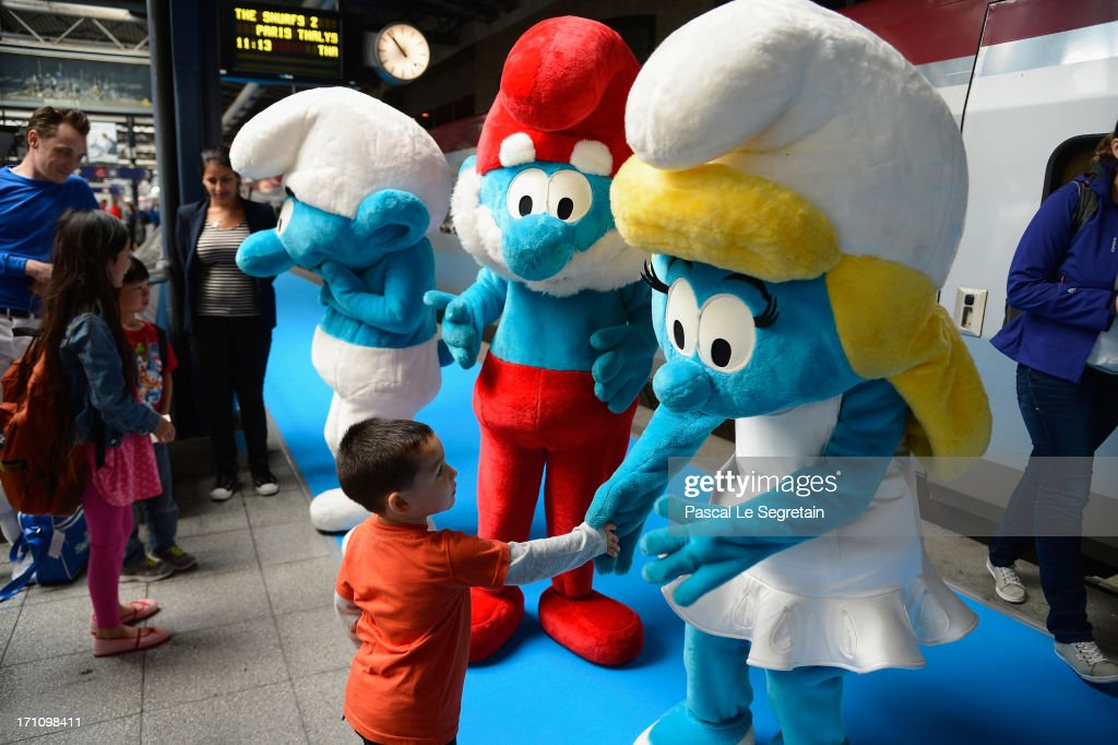 Young children meet with Smurf characters as Smurf Ambassadors prepare to board a high speed train from Brussels to Paris as part of Global Smurfs Day celebrations on June 22, 2013 at Brussels railway station, Belgium.