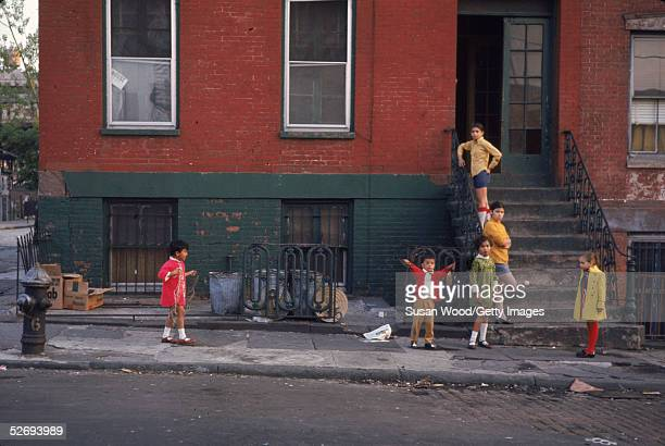 Young children model brightly colored clothing and coats on and around a stoop during a children's fashion photo shoot on a street in lower Manhattan...
