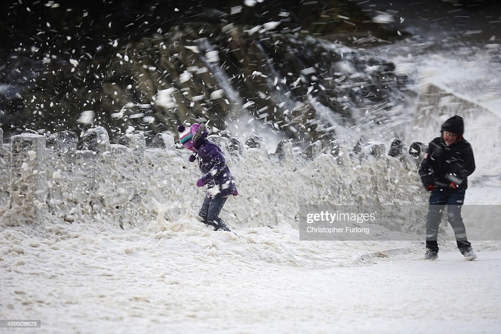 Young children play in a blizzard of sea foam whipped up by the wind near Trearddur Bay on December 27, 2013 in Anglesey, United Kingdom. A yellow 'be aware' warning has been issued for many parts of Britain as the country is affected by gale force winds and heavy rain.