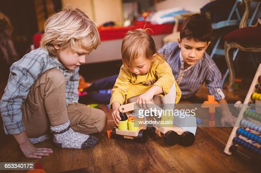 Young children playing with toys on bedroom floor : Photo