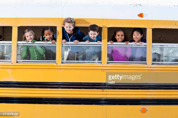 Young children poking heads out school bus windows
