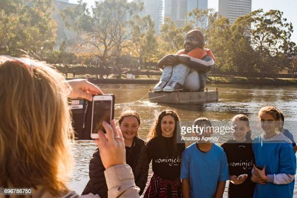 Young children pose for a photo in front of the travelling artwork titled 'Inflatable Refugee' on the Yarra River on June 17 2017 in Melbourne...