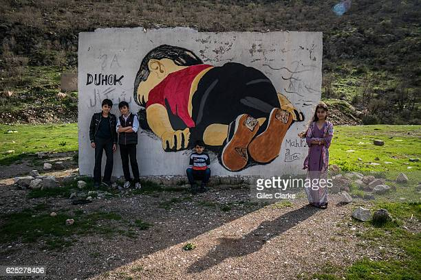 KURDISTAN Young children pose for a portrait behind a mural of a threeyearold Syrian boy of Kurdish ethnic background whose image made global...