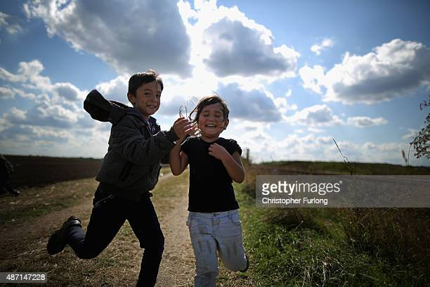 Young children race each other as theycross the border from Serbia into Hungary along the railway tracks close to the village of Roszke on September...