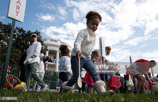 Young children roll Easter eggs on the South Lawn of the White House during the annual White House Easter Egg Roll March 28 2016 in Washington DC...