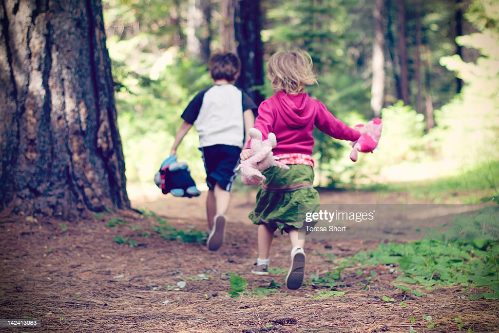 Young children running through trees : Stock Photo