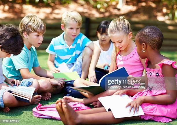 Jeunes enfants assis sur l'herbe et à étudier