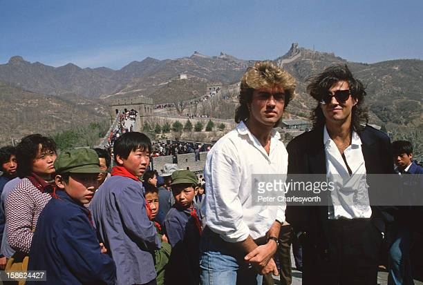 Young children sporting 'Mao' jackets and caps gape at George Michael and Andrew Ridgeley of the pop group Wham who are visiting the Great Wall as...