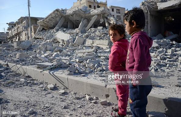 TOPSHOT Young children stand in a destroyed street in the northwestern border town of alBab on February 23 after Turkishbacked Syrian rebels fully...