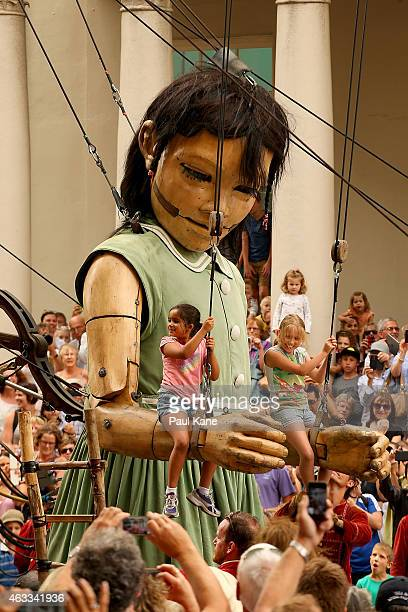 Young children swing on the arms of the little girl Giant on Hay Street during the Perth International Arts Festival on February 13 2015 in Perth...