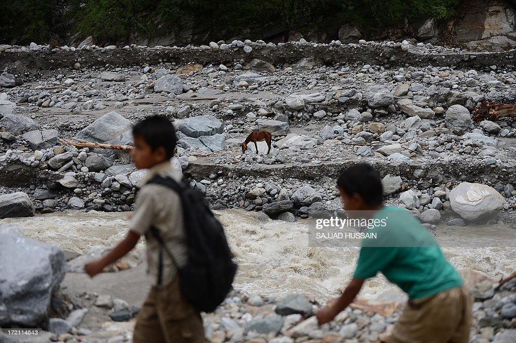 Young children walk beside a river as a mule grazes in Sonprayag on July 2, 2013, in a flood affected area of the northern Indian state of Uttrakhand. Construction along river banks will be banned in a devastated north Indian state amid concerns unchecked development fuelled last month's flash floods and landslides that killed thousands, the state's top official said. The Chief Minister of Uttarakhand, Vijay Bahuguna, also announced that a regulatory body would be set up to scrutinise future construction as the Himalayan state begins the herculean task of rebuilding following the June 15 floods.
