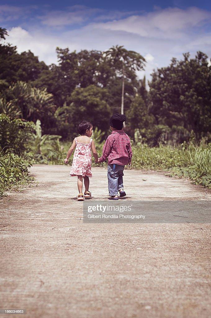 Young children walking hand in hand : Stock Photo