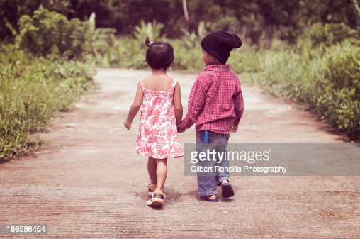 Young children walking hand in hand : Stock Photo
