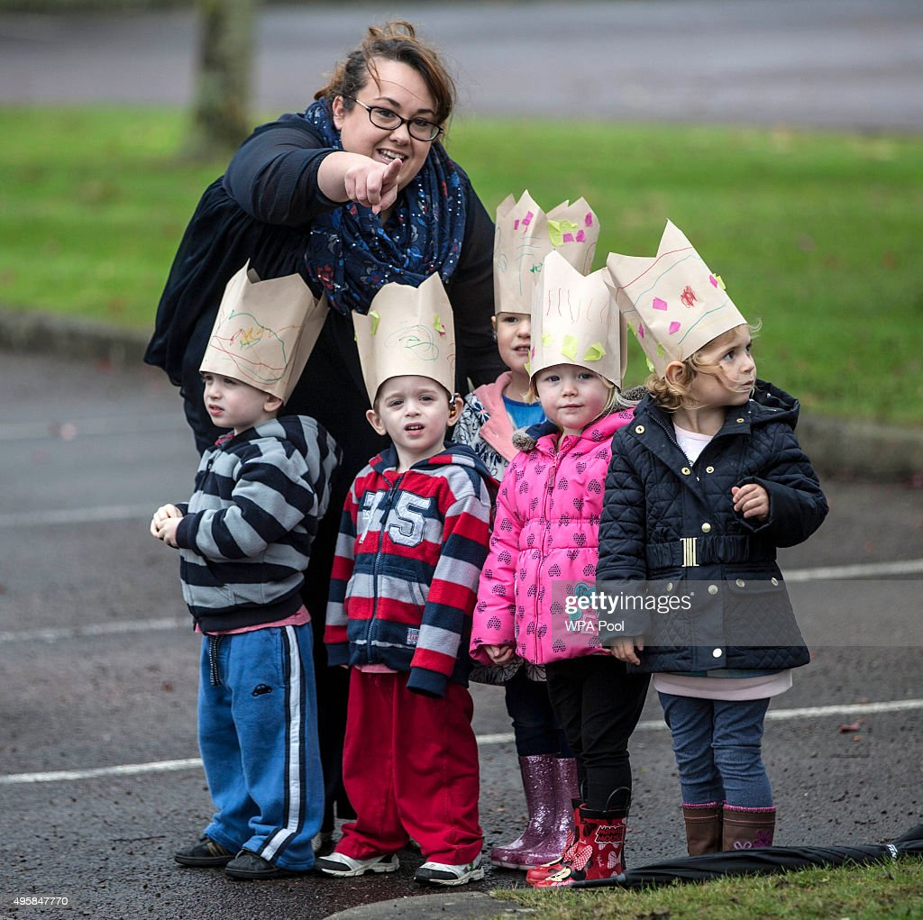 Young children wear paper crowns as they wait for Queen Elizabeth II to visit Imjin barracks on November 5, 2015 in Innsworth, Gloucestershire, United Kingdom.