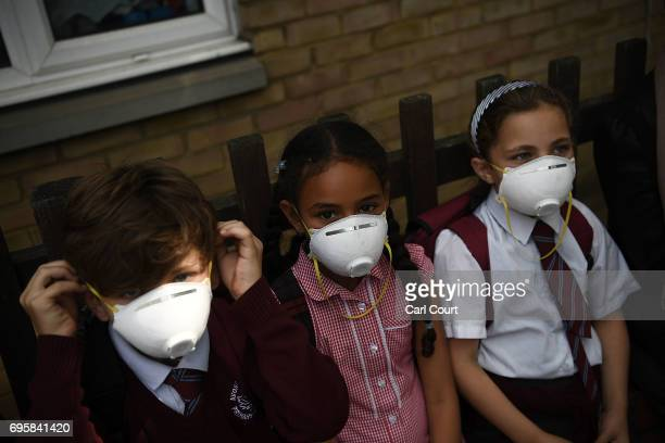 Young children wear protective face masks near the burning 24 storey residential Grenfell Tower block in Latimer Road West London on June 14 2017 in...