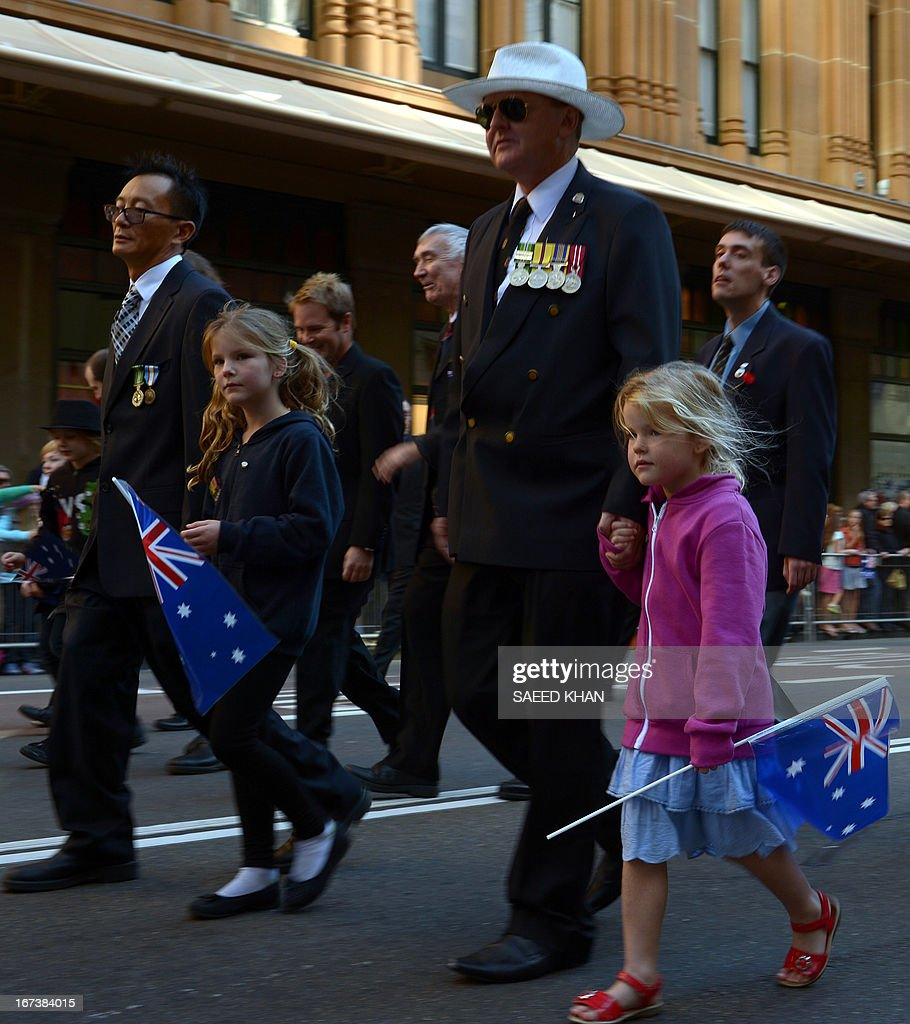 Young children with flags march along with elders as they participate in the Anzac Day march in Sydney on April 25, 2013. Tens of thousands of Australians and New Zealanders turned out on April 25 to honour their war dead, with moving tributes to fallen mates and calls not to forget those injured in conflict. AFP PHOTO / Saeed Khan
