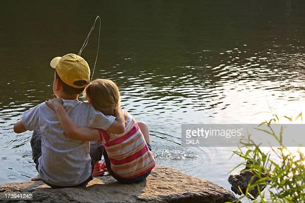 Jeunes enfants et des amis assis à l'étang/lake