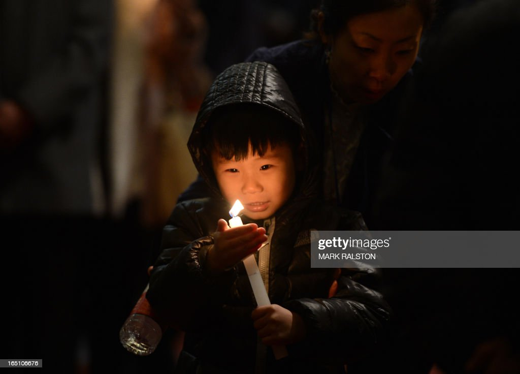 A young Chinese Catholic holds a candle during an Easter service at the Cathedral of the Immaculate Conception in Beijing on March 30, 2013. Experts estimate that there are as many as 12 million Catholics in China, with about half in congregations under the officially-administered Chinese Catholic Patriotic Association. The rest belong to non-sanctioned or so-called underground churches.. AFP PHOTO/Mark RALSTON