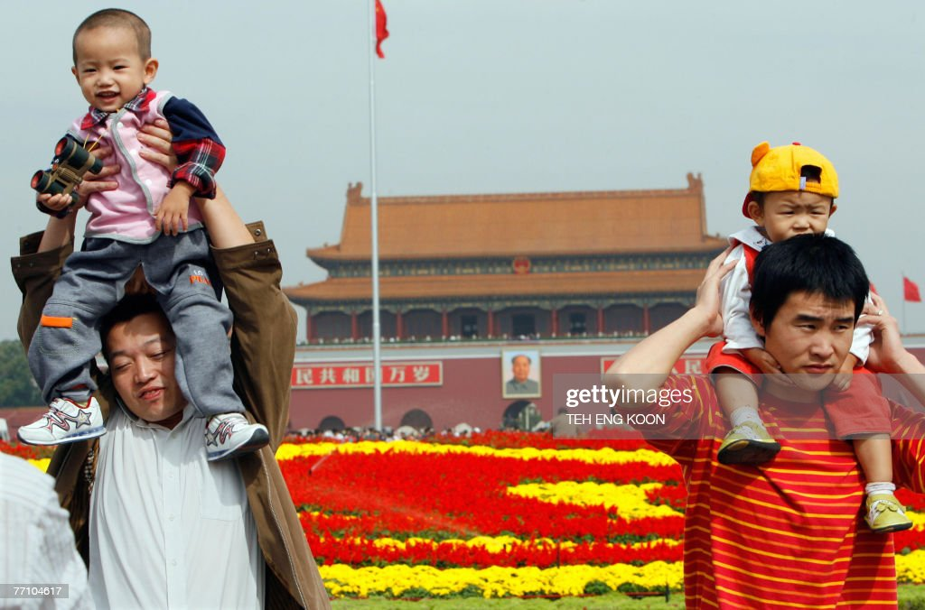 Young Chinese children sit on their fathers shoulders at the Tiananmen Square in Beijing, 29 September 2007. The Chinese capital is gearing up for its 58th National Day celebration 01 October and the 17th Communist Party Congress in mid-October, which could lead to personnel changes in the top echelons of power and will set China's political and economic course for the next five years. AFP PHOTO/TEH ENG KOON